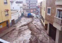 Rue inondée d'eau qui emporte tout sur son passage